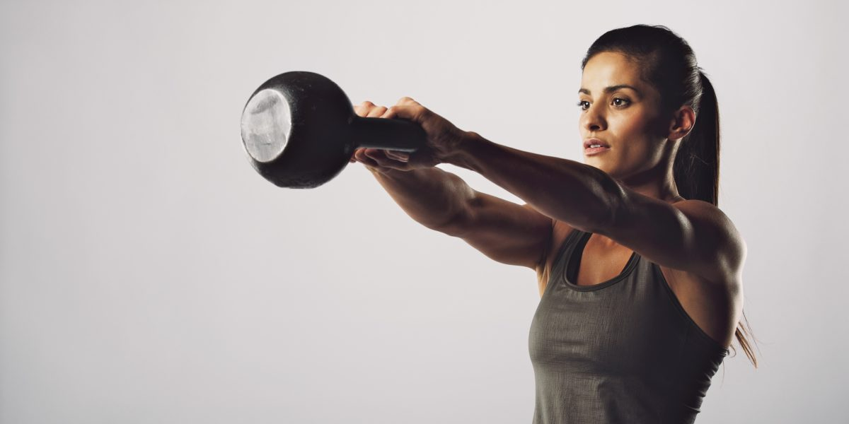Young fitness female exercise with kettle bell.